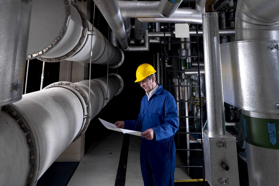 Engineer inspecting air conditioning pipes