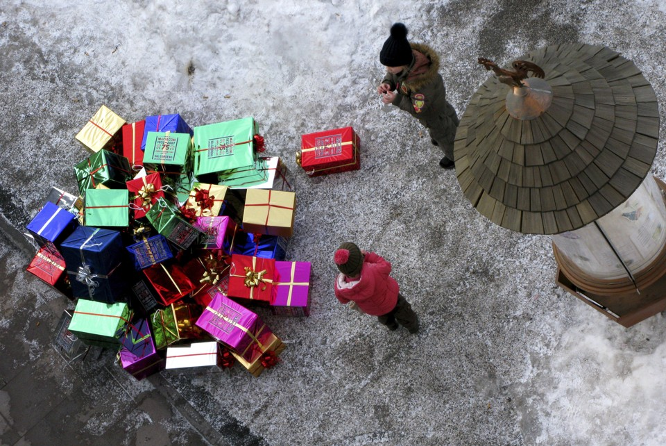 Children look at wrapped gifts on the ground as a man dressed as Santa Claus (not pictured) climbs a building to hang them during a ceremony in the northern Italian ski resort of Selva Di Val Gardena December 8, 2007.   REUTERS/Alessandro Bianchi   (ITALY) - RTX4J9A