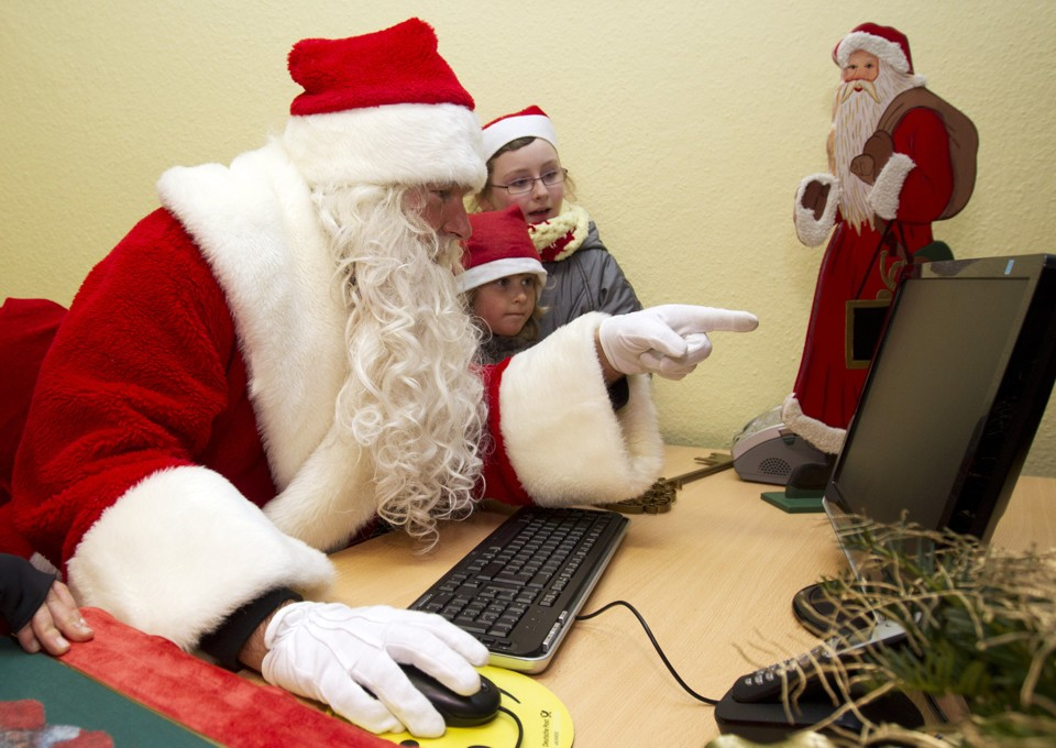 A man dressed as Father Christmas and children look at a computer screen at a special Christmas post office in the village of Himmelpfort (Heaven's Gate), north of Berlin November 10, 2011. The post office in the village of Himmelpfort opened on Thursday with a special Christmas service, replying to mails addressed to Santa Claus that were sent by children from all over the world. Some 20,000 letters already arrived at the post office and organisers expect to receive some 280,000 letters and wish lists from children writing in 17 languages.  REUTERS/Thomas Peter (GERMANY - Tags: RELIGION SOCIETY) - RTR2TTX2