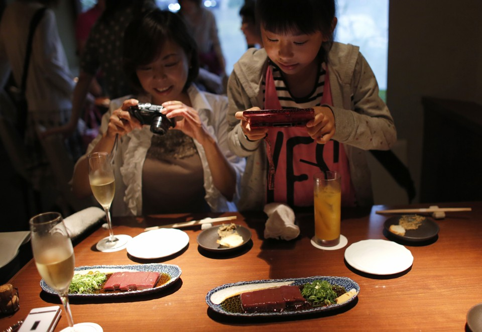 Yurika Miki (R) and her mother Yoshiko take photos of raw beef liver sashimi before eating them at a restaurant in Tokyo June 28, 2012. While Japan has a reputation as the home of sushi and sashimi, one item is about to be taken off the menu as Japan's government looks to ban the popular dish of raw liver in sashimi style. The dish, which consists of raw beef liver sliced up into bite sized chunks and then served with onions and sauce had become a popular dish across the country. Picture taken June 28, 2012. REUTERS/Toru Hanai (JAPAN - Tags: BUSINESS FOOD SOCIETY) - RTR34CQ5